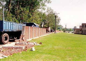 Pobořená cihlová zídka u fotbalového hřiště (lokalita 2 na obr.8). Foto autor.